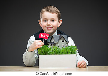 Little boy keeping house model and sold tablet - Portrait of...