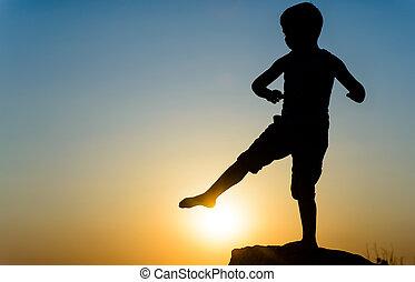 Little boy kicking the setting sun - Little boy silhouetted...