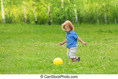 little boy kicking yellow ball