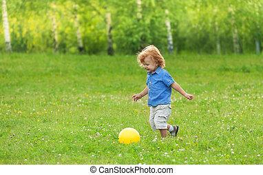 little boy kicking yellow ball