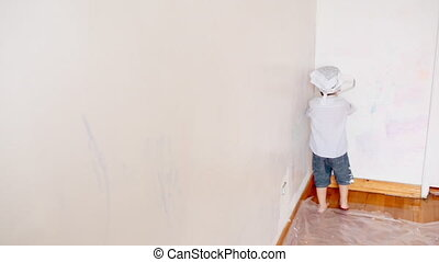 little boy kid painting the white wall at home. Decorating new apartment.