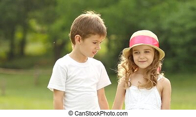 Little boy kisses the girl on the cheek, she is embarrassed...