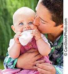 Little boy kissing baby sister