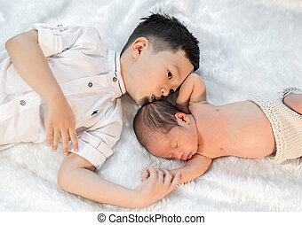 little boy kissing his newborn baby brother on bed