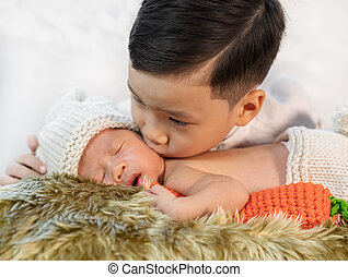 boy kissing his newborn baby brother