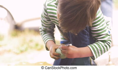 Little boy kneeling and coloring an easter egg with a crayon...