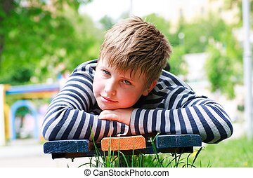boy lay on a bench in the park