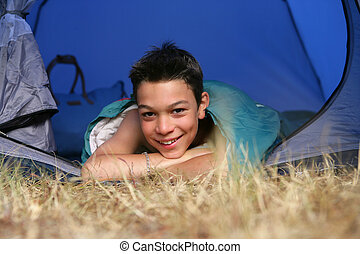 Little boy laying in a tent