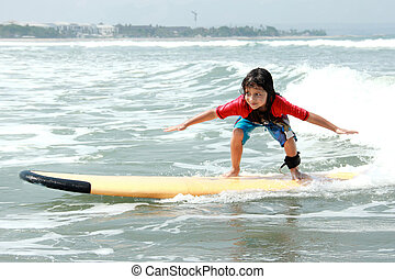 little boy learn to surf at ocean