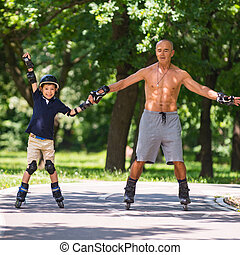 Little boy learning how to roller skate with his grandfather