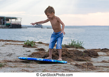 Little boy learning how to surf