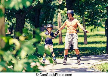 Little boy learning roller skating in park