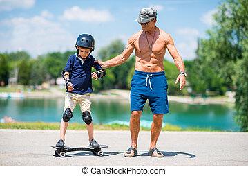 Little boy learning snakeboard, grandpa helping