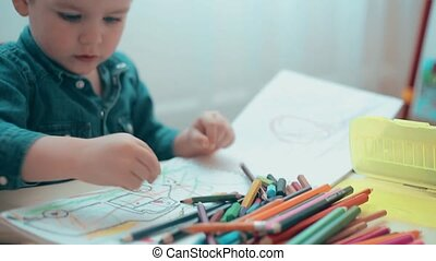 Little boy learns to draw with colored pencils and crayons
