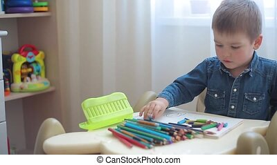 Little boy learns to draw with colored pencils