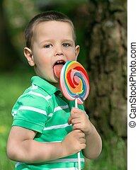 Little boy licking a lollipop
