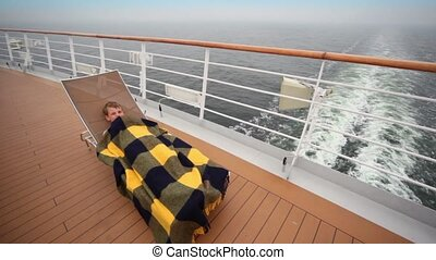 Little boy lies under plaid on deckchair at deck of ship...