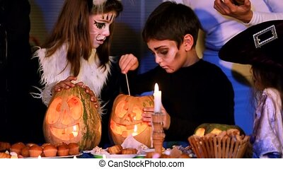 Little Boy Lighting Halloween Candle Inside Pumpkin