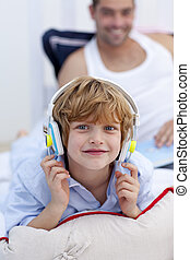 Little boy listening to music in bedroom with headphones on
