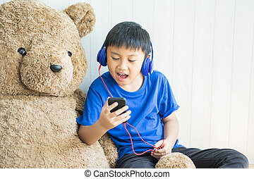 Little boy listening to music on bed in bedroom