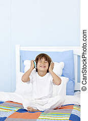 Little boy listening to music on headphones in his bed