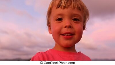 Little boy looking at camera in sunset