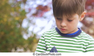 Little boy looking down focused and concentrating on something