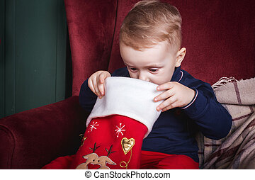 little boy looking inside a christmas stocking