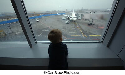 Little boy looking out the window at airport
