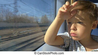 Little boy looking out train window on sunny day