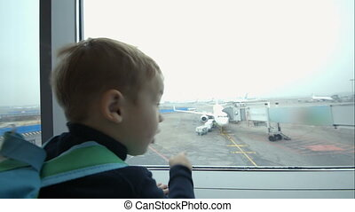 Little boy looking out window and pointing at plane