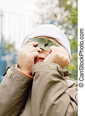 Little boy looking through leaf