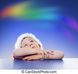 Little boy looking up to rainbow on sky