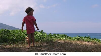 Little boy looks at sea from height - Little kid boy looking...