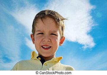 little boy looks down on blue sky background horizontal
