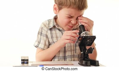 Little boy looks into microscope and setting it up