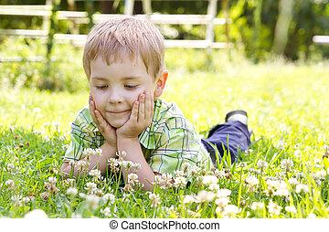 Little boy lying in clover flower field, hands under the cheeks Sunny summer, spring day
