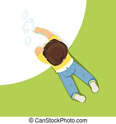 Little boy lying on his stomach and drawing clouds using pencil, top view of child on the floor