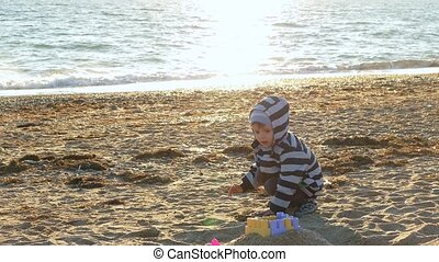 little boy make a sand castle on the beach.