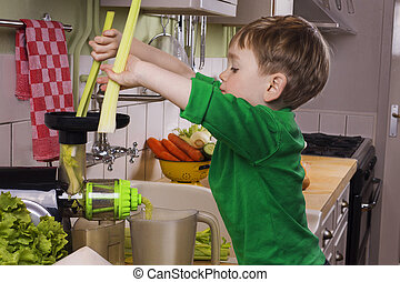 Little boy making green juice
