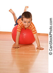 Little boy playing with a huge red gymnastic ball