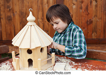 Little boy making the last finishing touches on a bird house...