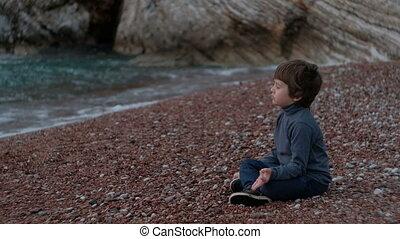 Little boy meditating sitting by sea outdoor.