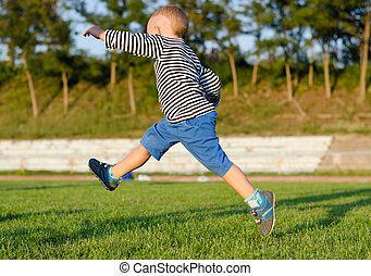 Little boy midair kicking a ball