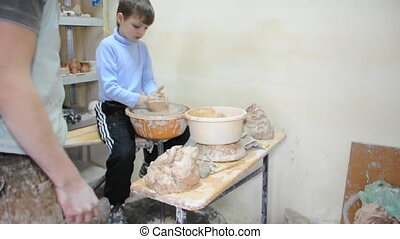 pottery - little boy modeling on pottery wheel and getting...