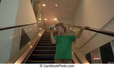 Little boy moves down the escalator holding white toy airplane in his hand. Freedom concept. Childhood concept. Children travel concept