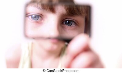 Little boy moves loupe in front of his face and enlarge it
