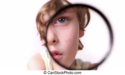 Little boy moves magnifying glass in front of his face and enlarge it