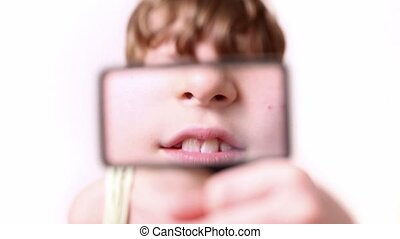 Little boy moves rectangular magnifying glass in front of...