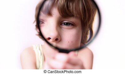 Little boy moves round loupe in front of his face and enlarge it, then put loupe away